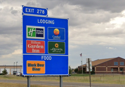 Exit 278 sign snowing lodging and food in Great Falls