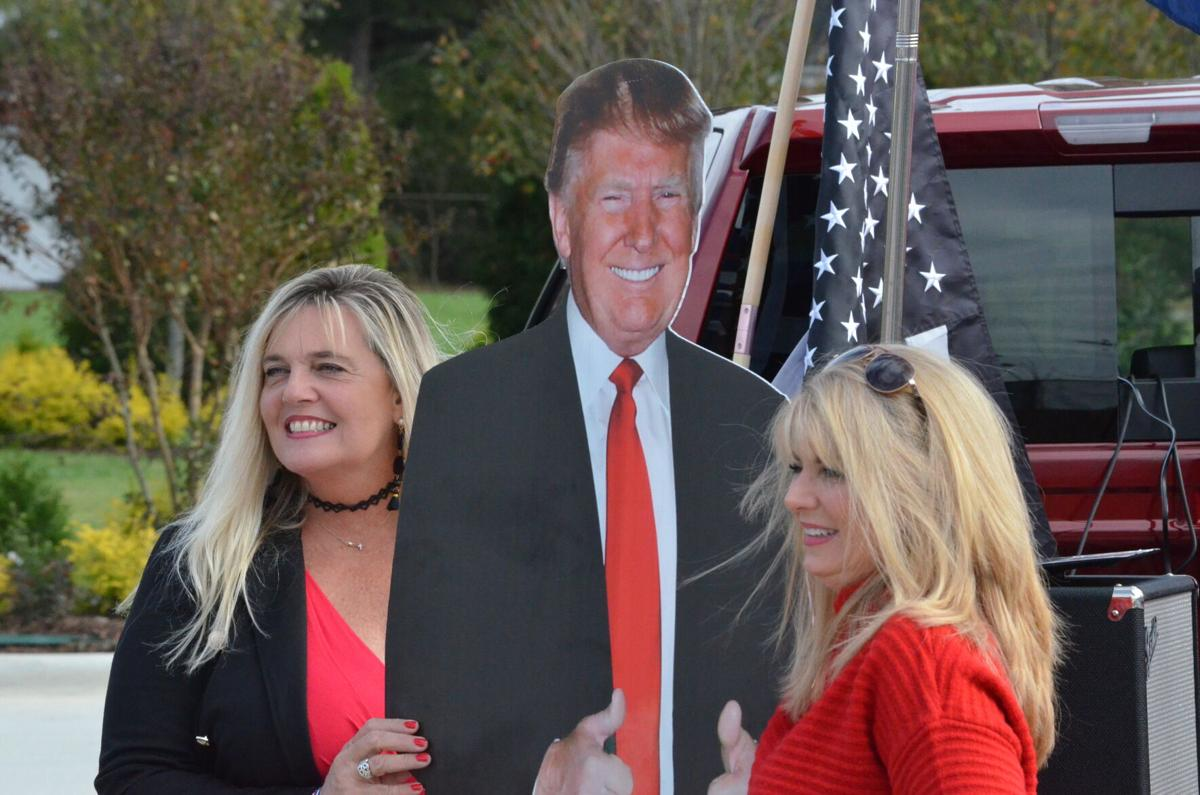 Sible Winebarger (left) and another supporter of Donald Trump stand with a cardboard cutout of the president before a parade in Mooresville on Saturday.