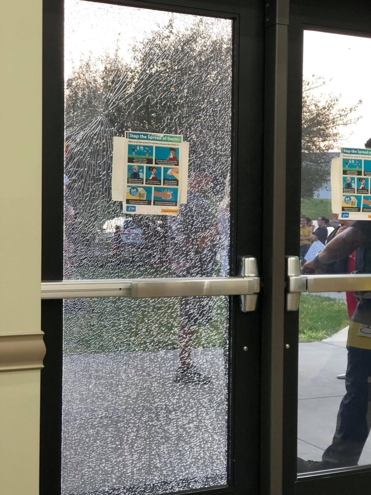 A door to the Career Academy & Technical School where Iredell-Statesville Schools held Monday's meeting was broken by protesters outside in Troutman on Monday.
