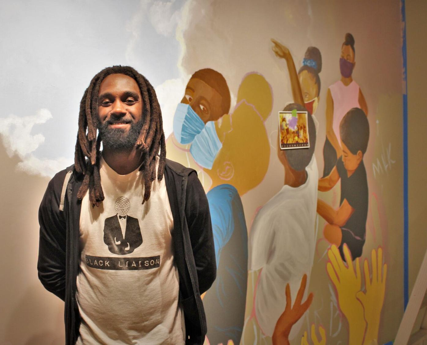 Broderick smiles in front of mural