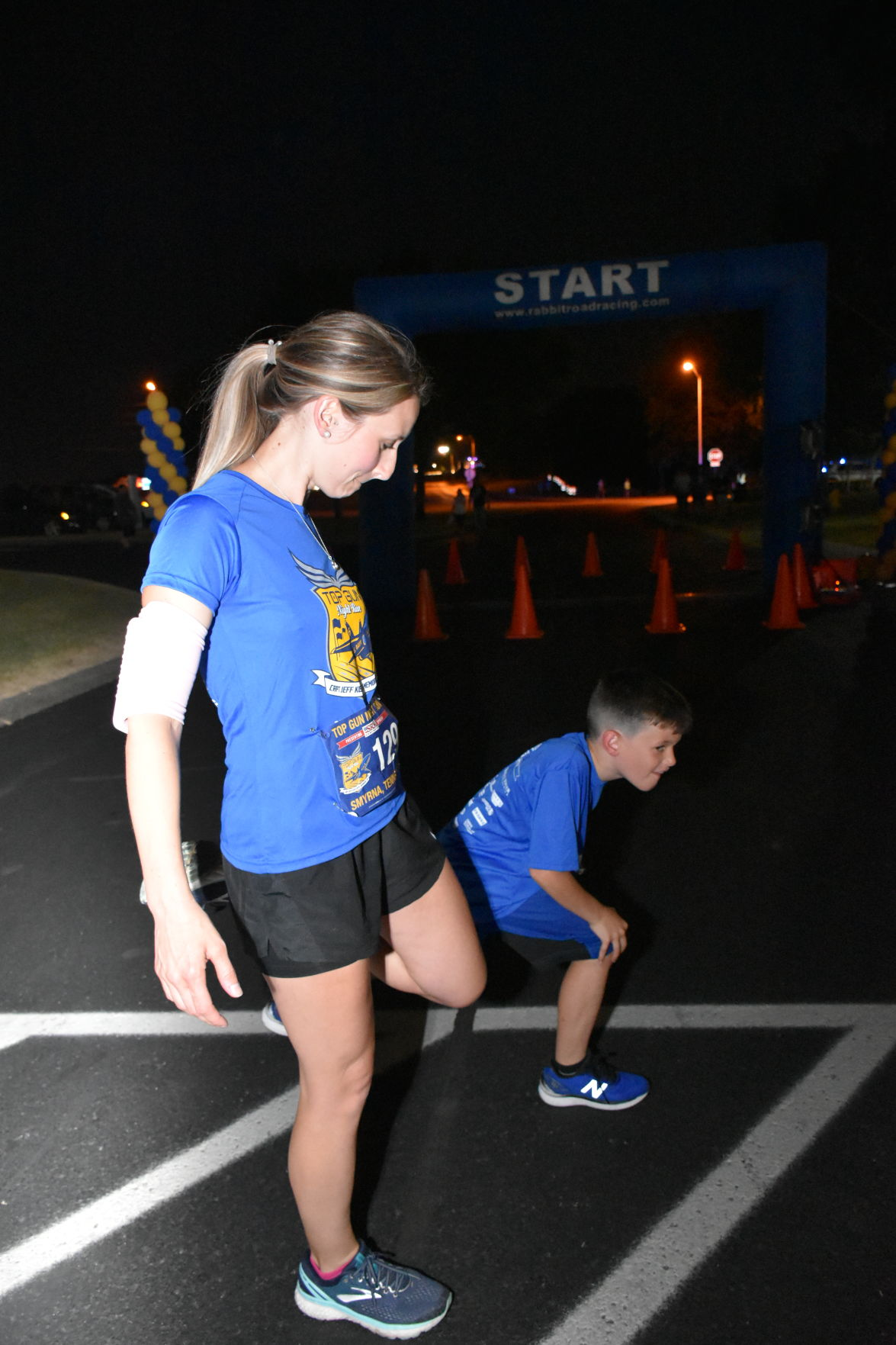 Jennifer Donaldson and her son, Brody, stretch before the Top Gun Night Run. The 6K was their second race together.