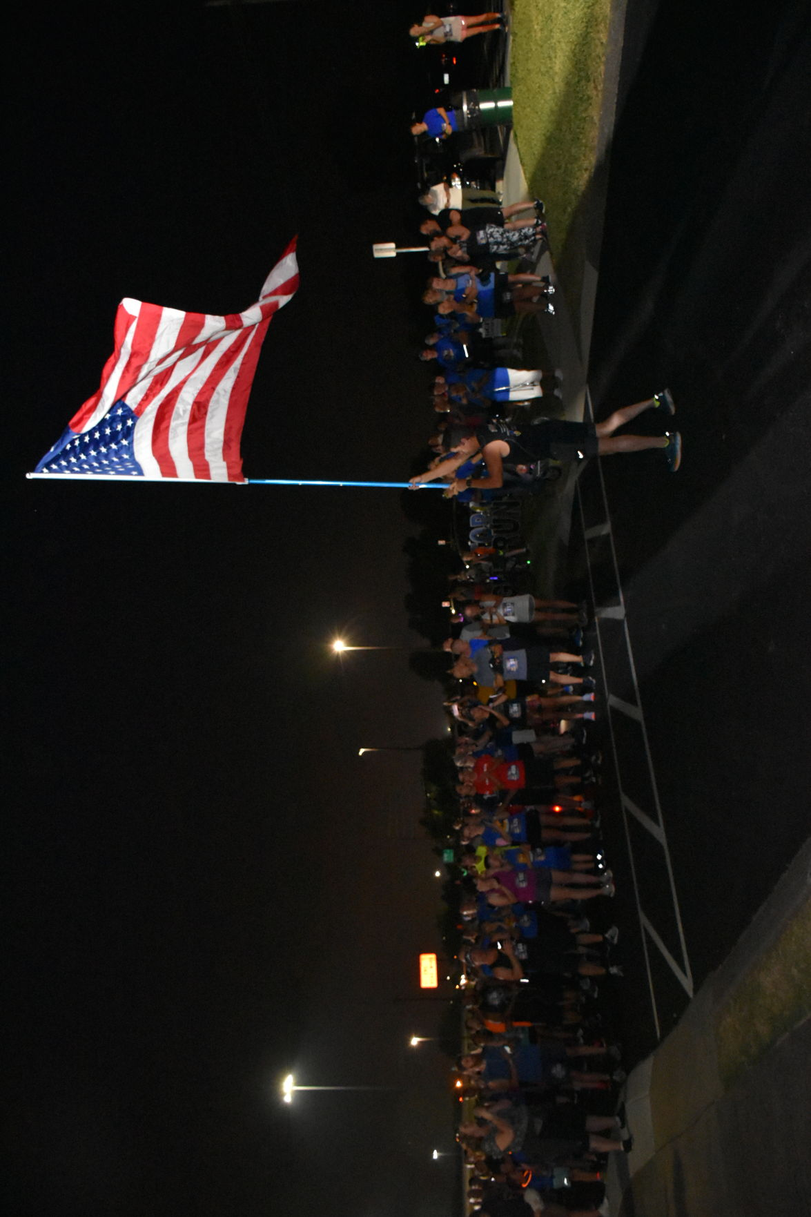 Top Gun Night Run participants recite the Pledge of Allegiance at the Smyrna Event Center starting line. Randy Woodward, a veteran wounded in combat, waves the U.S. flag.