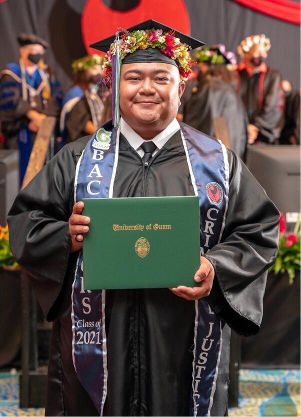 Daniel Kintol holds his University of Guam Diploma at the Northern Marianas College commencement ceremony on May 21, 2021.