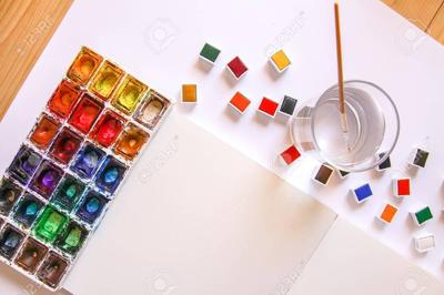Watercolor paints, brushes, water in glass and paper on white background. Flat lay, top view