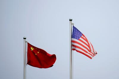 Chinese and U.S. flags flutter outside a company building in Shanghai