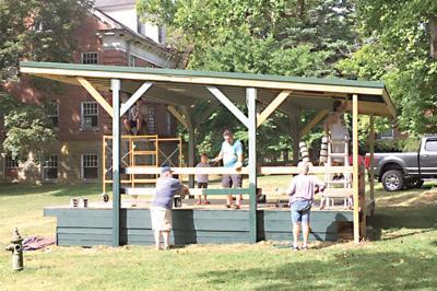 Volunteers help paint Mayfest stage