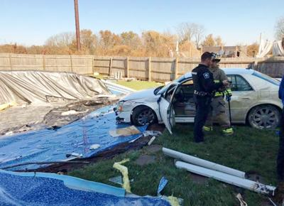 Car sails through closed garage, stopped by pool
