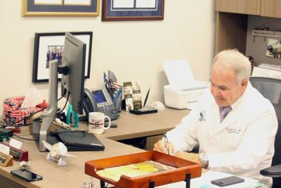 Dr. Harmon works at his desk