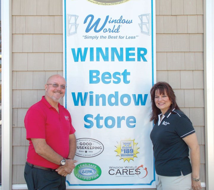 Photo of Window World owners in front of banner