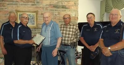 Merritt Warren is presented a plaque in his home