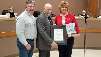 Arnold Commission on Aging and Disabilities chairman Bill Knittig, left, and Mayor Ron Counts, accept the city's certificate declaring it part of the AARP Network of Age-Friendly States and Communities from Sheila Holm, community outreach director for AARP in St. Louis, at a Feb. 20 City Council meeting.