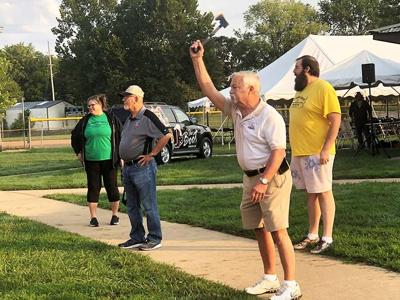 Crystal City Mayor Tom Schilly throws and ax during the Mayor's Challenge this morning, and Festus Mayor Sam Richards, in ballcap, looks on.