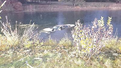 Firefighters rescued a woman from this car submerged in a pond near Six Flags.
