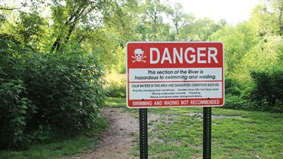 A sign at Cedar Hill Park warns people about the dangers of swimming in the Big River there.
