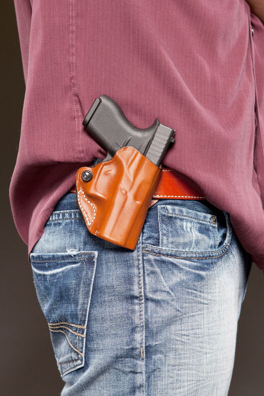 Side view of a 9 mm pistol in a holster on a man's belt.