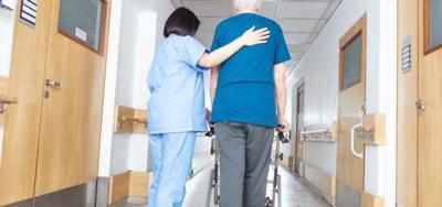 Asian nurse helping elder man walking in rehab facility