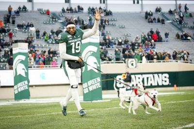 A college football player's parents died before his Senior Day. So he walked onto the field with his two dogs