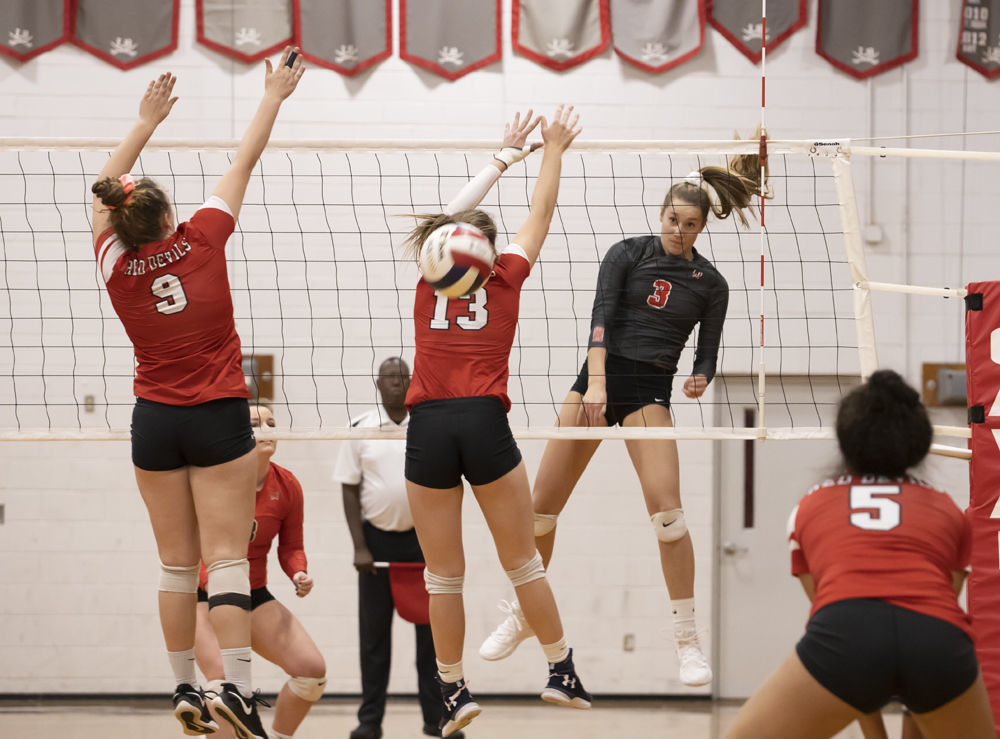Lord Botetourt's (3) Miette Veldman spikes the ball past Rustburg's (9) Rachel Sledd and (13) Eden Bigham while (5) Meah Coles looks on.