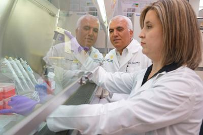 Dr. Saleh Naser and Dr. Latifa Abdelli work in a lab at the Burnett Biomedical Sciences Building.