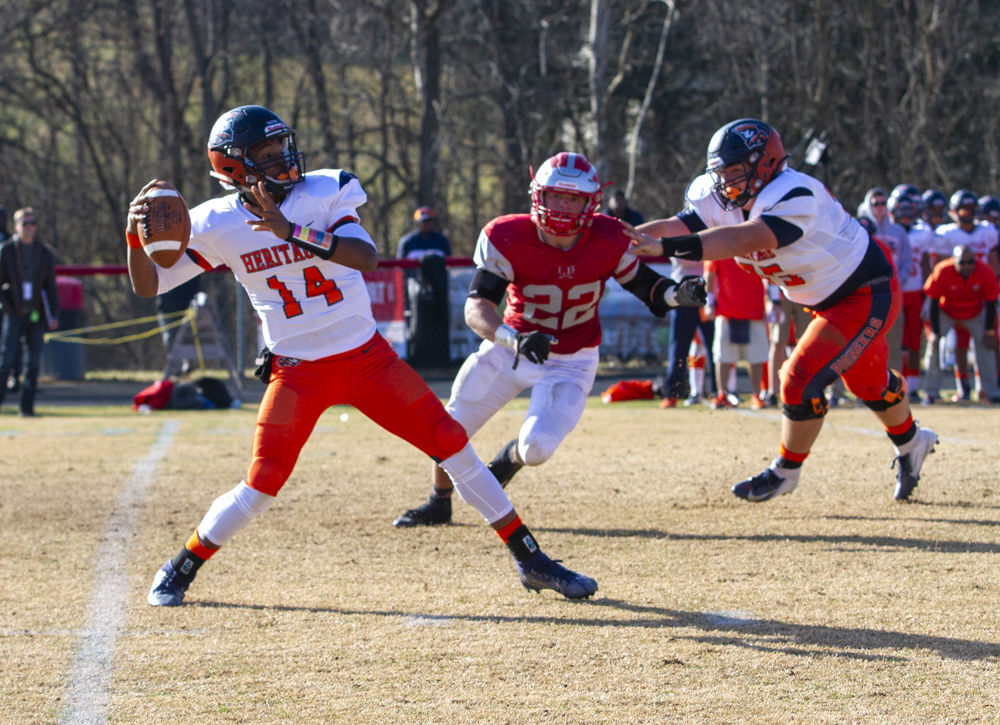 Heritage's (14) Kameron Burns loads up a pass as teammate (55) Mike Williams tries to block Lord Botetourt's (22) Ethan Clower. The pass is completed for a long touchdown.