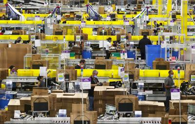 Employees at packing stations are seen at Amazon's Kent, Wash., fulfillment center on June 11, 2020.