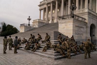 National Guard eat breakfast while sitting on the steps to the House of Representatives on Monday, Jan. 11, 2021, on the U.S. Capitol Building grounds, as heightened security measures are in place nearly a week after a pro-Trump insurrectionist mob breached the security of the nation's capitol while Congress voted to certify the 2020 election results in...
