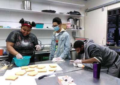 Ke'Niyah Smith, Earl Veney and Tyquon Clayton have fun preparing French toast.