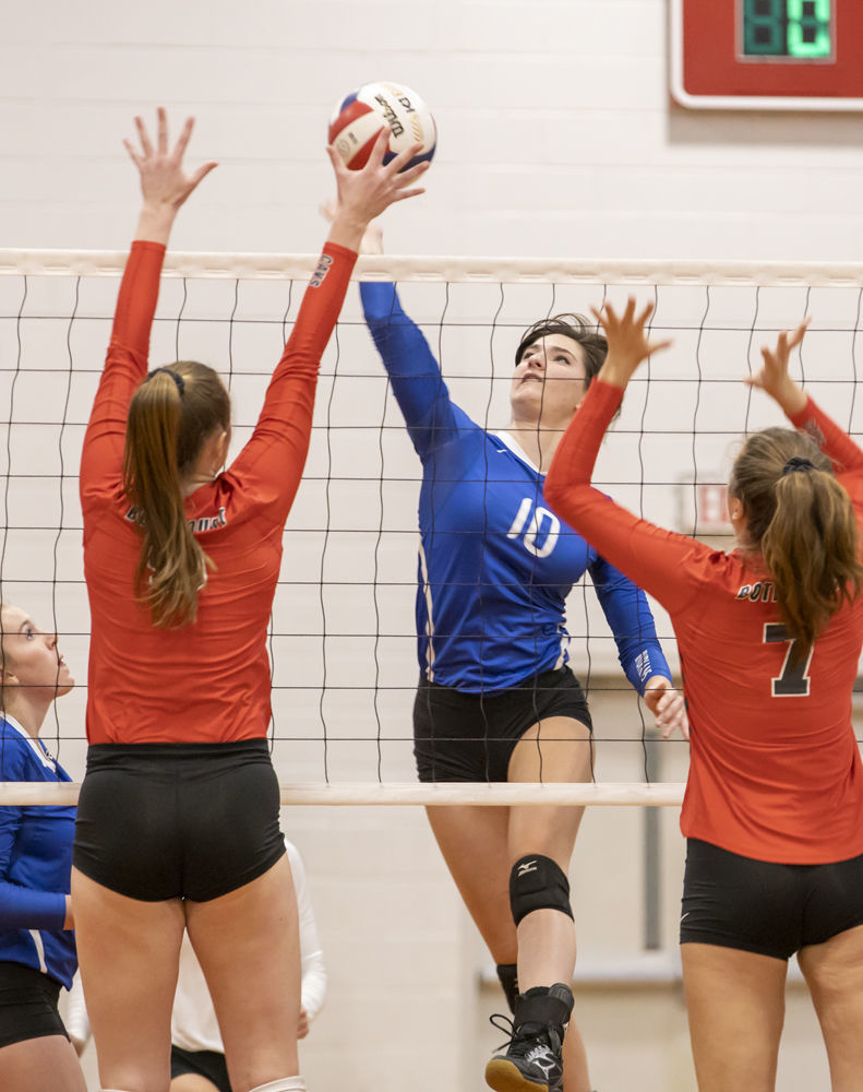Fort Defiance's (10) Caroline Simonetti strikes the ball hoping to get it past Lord Botetourt's (9) Taylor Robertson and (7) Parker Hudson.