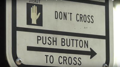 Sign at Stop Lights to Cross Walk