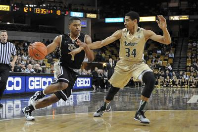 41f056d72ca UCF men's basketball's point guard B.J Taylor, left, dribbles past a  University of South Florida defender on Feb. 11, 2015. Taylor missed the  entire ...