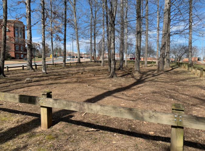 The cemetery is surrounded by a wooden brown fence.