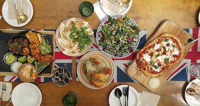Table with pizza, hummus, and other international foods