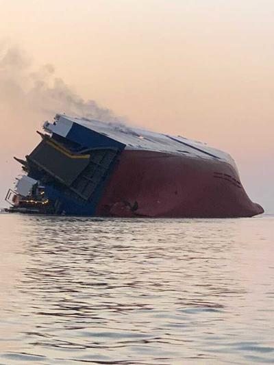 Trapped crew members rescued off overturned ship after fire