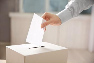 Closeup of hand inserting envelope in ballot box