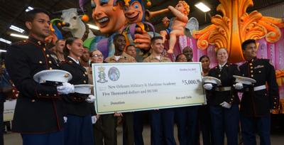 Students of the New Orleans Military and Maritime Academy accept a donation from the Rex and Zulu Mardi Gras krewes STAFF PHOTO BE DOUG MacCASH.jpg