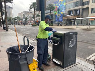Downtown Development District employee sanitizes a trash can