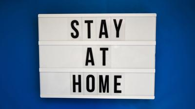 Lightbox with text STAY AT HOME on blue background