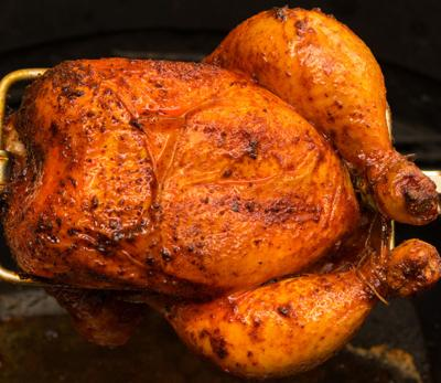 Charred rotisserie chicken over open flames in a barbecue. room for text