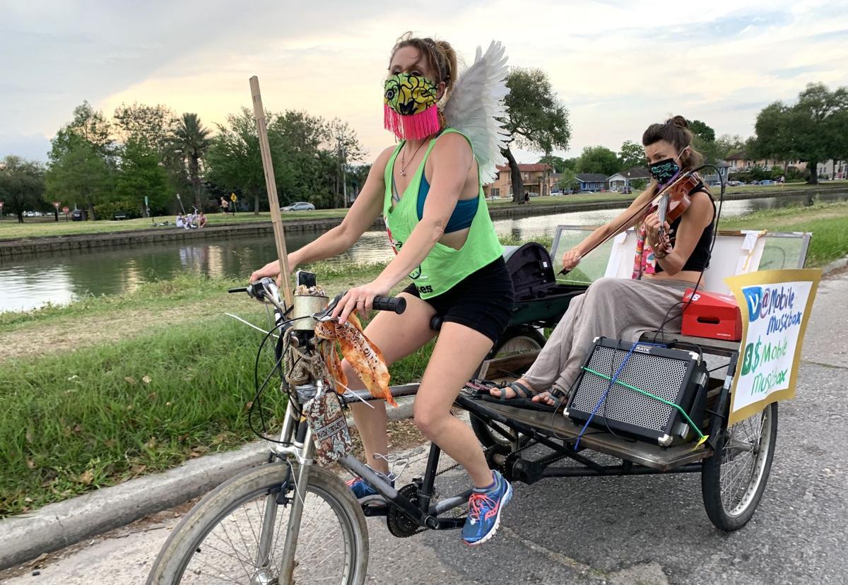 French Quarter street musician Anna Roznowska and pedicab operator Sarah Grant serenade Bayou St. John with their Mobile Music Box