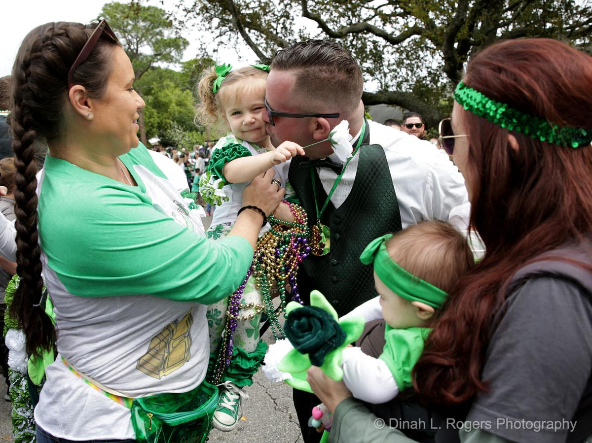 Leslie Scala holds her niece Leah Faurie, 2, as she gets a kiss from her father Larry as he passes during the Metairie Road 2019 St. Patrick's Day Parade