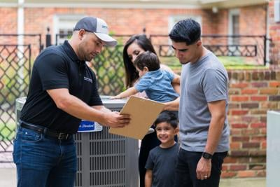 Client talking to American Standard technician while his baby touches the AC in the background