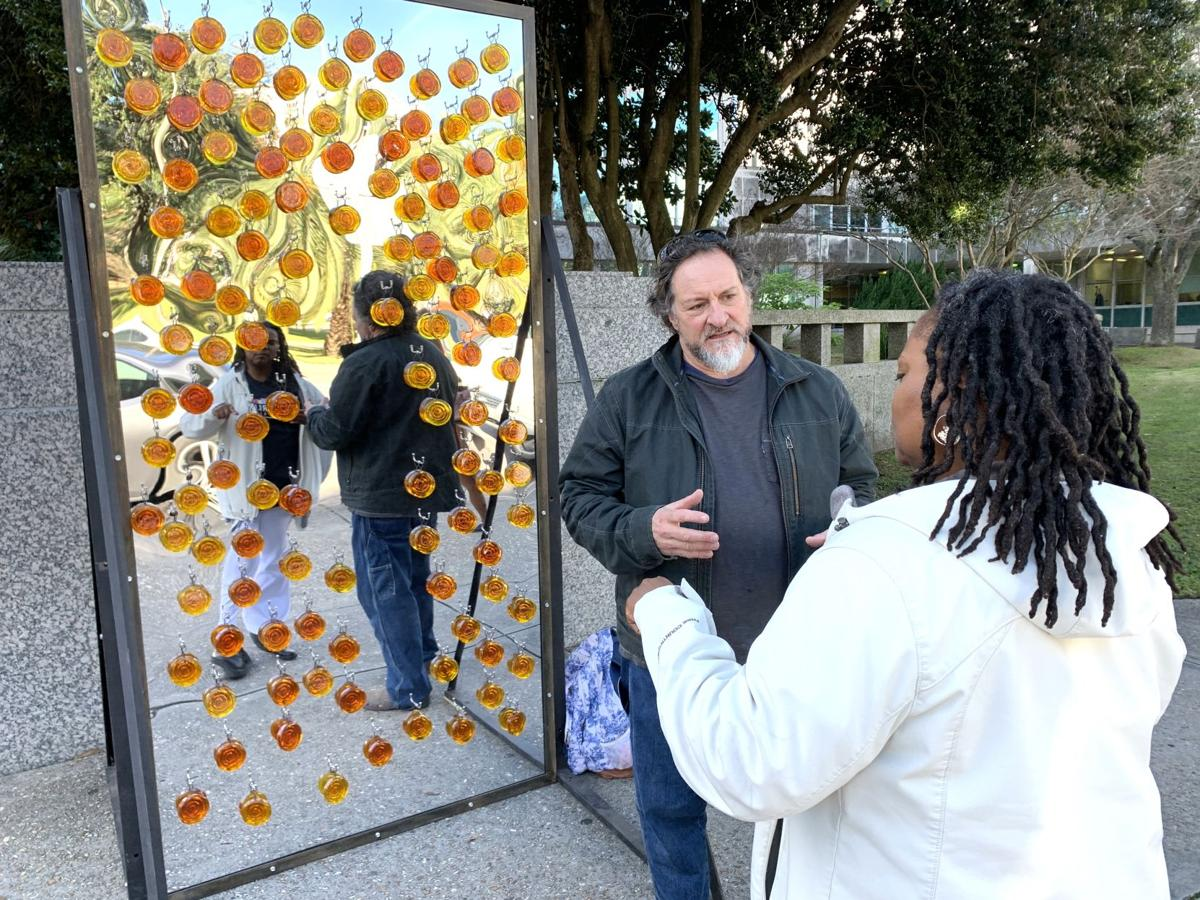 Artist Mitchell Gaudet discusses his artwork 'Murder Rate 2019' with Shakrani Gray near the steps to City Hall.