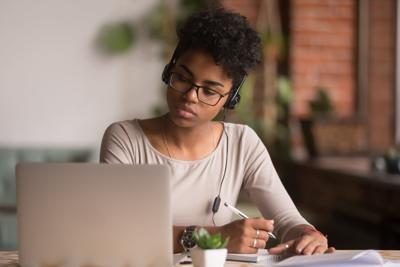 Focused mixed race woman wearing headphones watching webinar write notes
