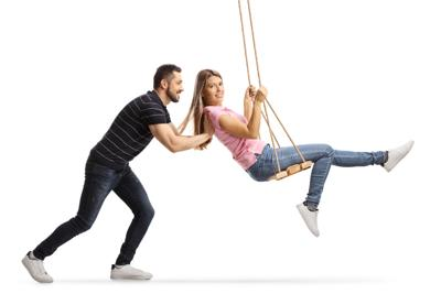 Guy pushing a young woman on a swing