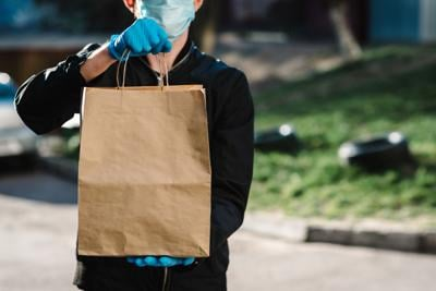 Courier in protective mask, medical gloves delivers takeaway food.  Employee hold cardboard package. Place for text. Delivery service under quarantine, 2019-ncov, pandemic coronavirus, covid-19.