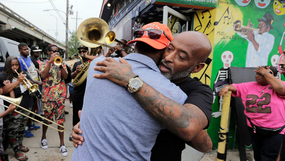 A second-line parade celebrating Dave Bartholomew flows through the Treme neighborhood of New Orleans