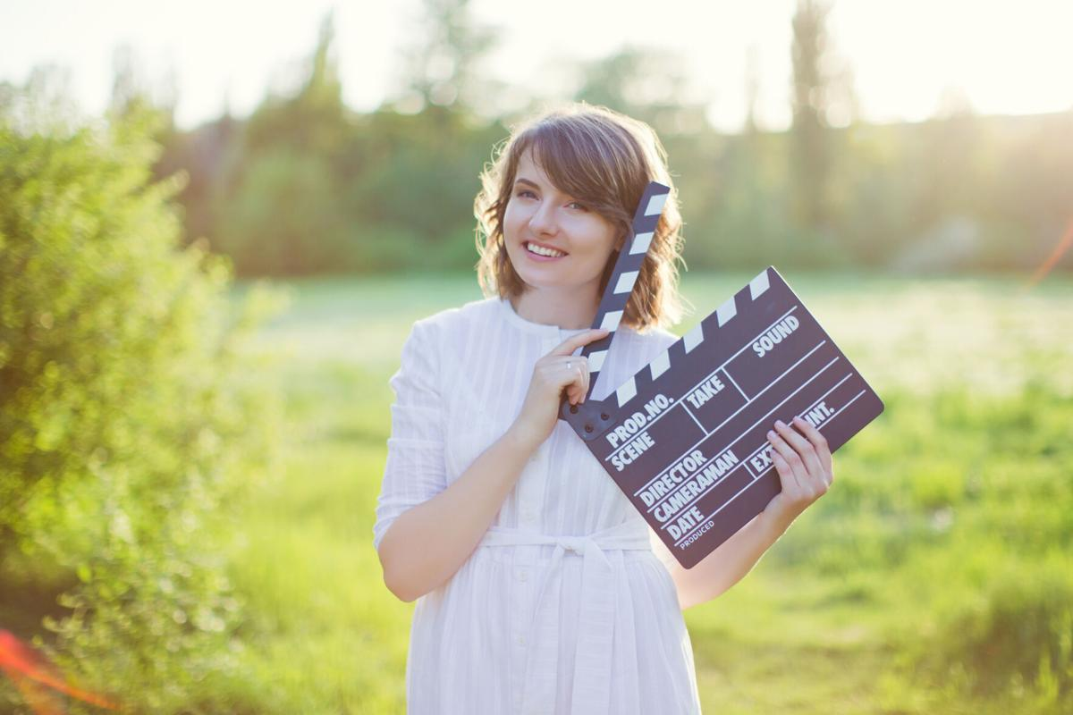 Woman holds clapper board at sunset