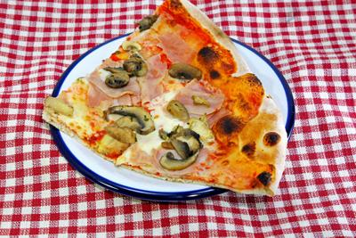 big slice of PIZZA at the Italian restaurant with red and white checkered tablecloth