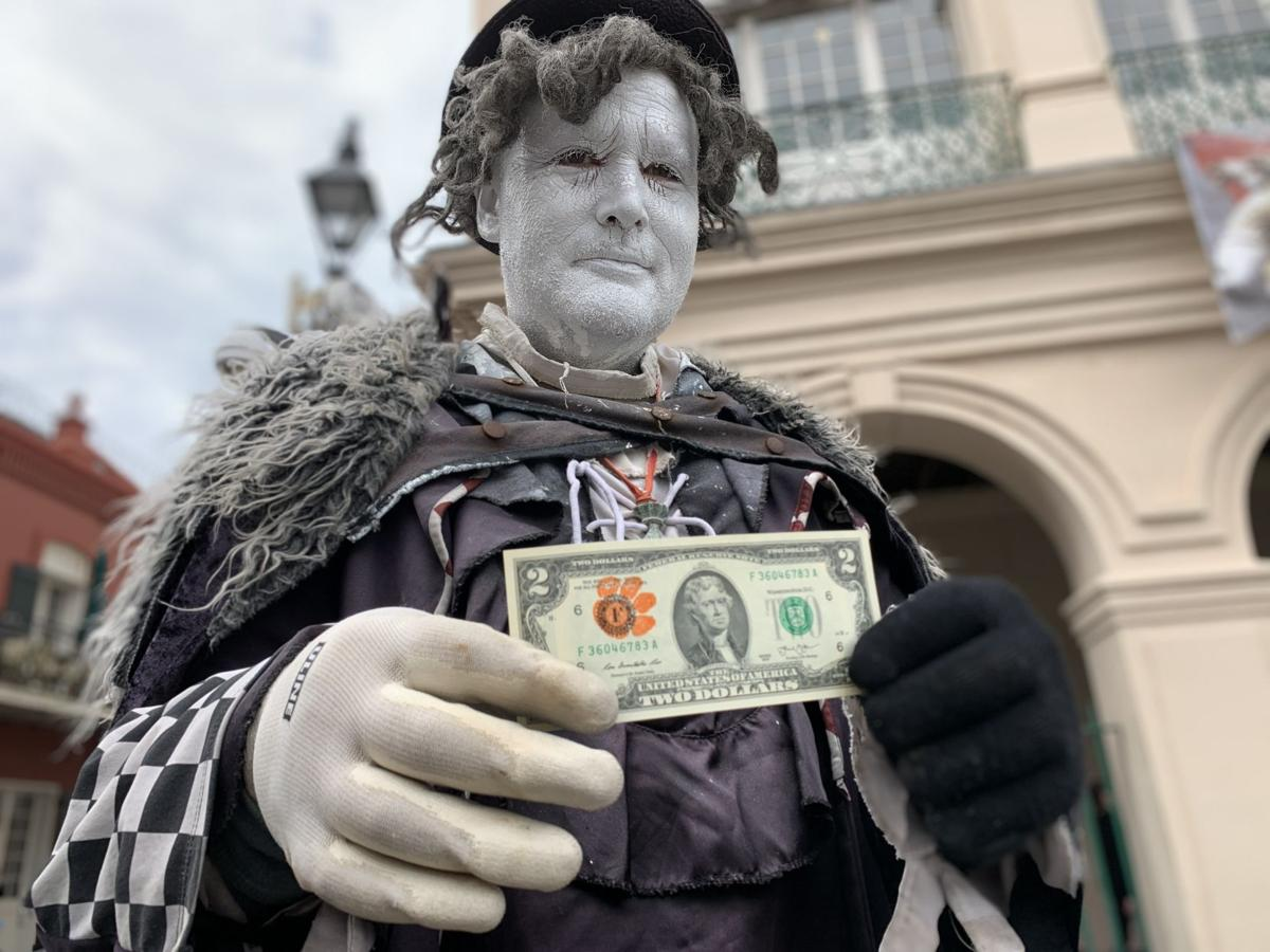 Jackson Square mime Noah Hansel with a Clemson two-dollar bill.