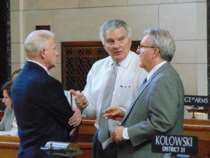 Appropriations Committee chair, Sen. John Stinner (center), speaks with Speaker Jim Scheer (to Stinner's left) and Sen. Matt Williams during legislative debate Wednesday evening.